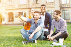 Cheerful young friends photographing themselves near university royalty free stock images