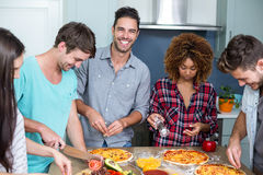 Cheerful young friends preparing pizza at home Stock Images