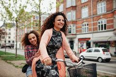 Cheerful young friends riding a bicycle in the city Royalty Free Stock Image