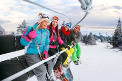 Cheerful friends on ski lift ride up on snowy mountain Royalty Free Stock Photography