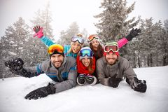 Cheerful friends on skiing laying together on snow. Cheerful young friends on skiing laying together on snow Stock Images