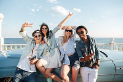 Cheerful young friends standing outdoors and showing peace sign. Group of cheerful young friends standing outdoors and showing peace sign Royalty Free Stock Photos