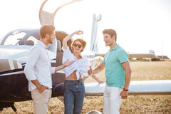 Cheerful young friends standing and talking on runway near airplane Royalty Free Stock Photo