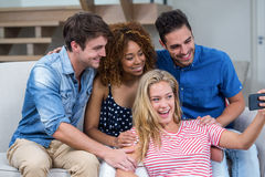 Cheerful young friends taking selfie at home Stock Photography