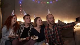 Cheerful, young friends or two couples having small, cozy birthday celebration, sitting together in festive cones on the