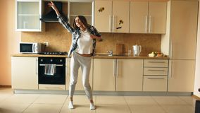 Cheerful young funny woman dancing and singing with ladle while having leisure time in the kitchen at home. In the morining royalty free stock photography