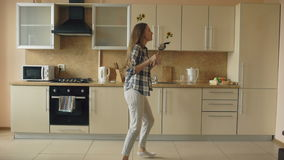 Cheerful young funny woman dancing and singing with ladle while having leisure time in the kitchen at home stock video footage