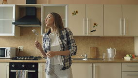 Cheerful young funny woman dancing and singing with ladle while having leisure time in the kitchen at home stock video