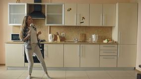 Cheerful young funny woman dancing and singing with ladle while having leisure time in the kitchen at home stock footage