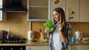 Cheerful young funny woman dancing and singing with lettuce microphone while cooking breakfast stock images