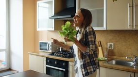 Cheerful young funny woman dancing and singing with lettuce microphone while cooking breakfast royalty free stock image