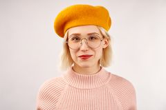 Cheerful young girl with an attractive appearance, a wide smile, dressed in yellow beret, warm pink knitted sweater stock image