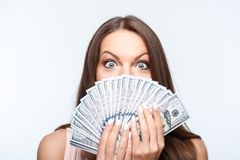 Cheerful young girl with a big amount of dollars. Attractive woman is holding money in her hands. She is covering her mouth with it. Her eyes are wide open with Royalty Free Stock Image