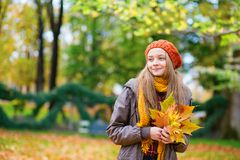 Cheerful young girl with bunch of leaves Stock Image