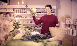 Cheerful young girl buying cauliflower at market Stock Photo