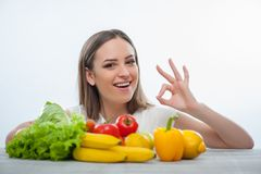 Cheerful young girl chooses to eat healthy food royalty free stock images