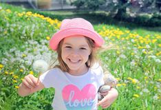 Cheerful young girl with dandelion. Cheerful young cute girl with dandelion on sunny field looking at camera Royalty Free Stock Image