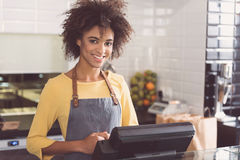 Cheerful young girl is expressing gladness at workplace. Friendly worker. Portrait of pleasant positive african woman is standing in organic store and laboring royalty free stock image