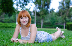 Cheerful young girl. Young cheerful girl has a rest on a green lawn Stock Image