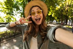 Cheerful young girl in hat and sunglasses stock photo
