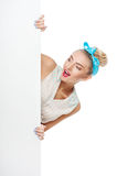 Cheerful young girl is hiding behind white Stock Image