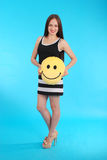 Cheerful young girl is holding a smiley face pillow Royalty Free Stock Images