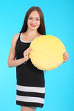 Cheerful young girl is holding a smiley face pillow Royalty Free Stock Photo