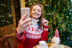 Cheerful young girl in holiday sweater in cafe decorated for Christmas royalty free stock images