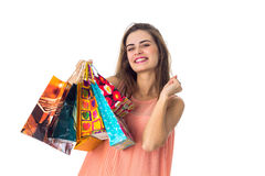 Cheerful young girl keeps many packages in hand isolated on white background Royalty Free Stock Photography