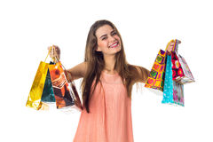 Cheerful young girl keeps two hands  lot of different packages, isolated on white background Royalty Free Stock Photo