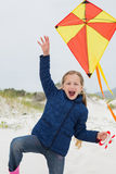Cheerful young girl with kite at beach. Portrait of a cheerful young girl with kite at the beach Stock Photo