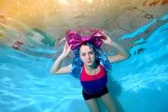 Cheerful young girl with large bow on your head swims in the pool underwater and looking at the camera. Portrait. Horizontal view. View from the bottom Stock Photo