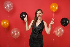 Cheerful young girl in little black dress celebrating, showing victory sign on bright red background air balloons. St royalty free stock image