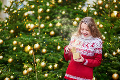 Cheerful young girl with little present box. Cheerful young girl opening little present box in hands near decorated Christmas tree, magic sparkles appear from Stock Photo