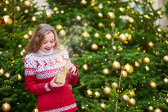 Cheerful young girl with little present box. Cheerful young girl opening little present box in hands near decorated Christmas tree, magic sparkles appear from Royalty Free Stock Images
