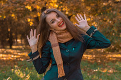 Cheerful young girl with long hair in the Park and rage lifted her hands up. Young girl with long hair in the Park and rage lifted her hands up stock images