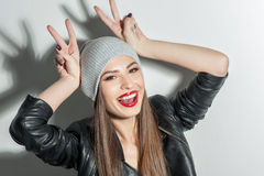 Cheerful young girl is making fun. Attractive woman is raising her arms to a head and making horns. She is looking at camera and smiling. The lady is wearing Royalty Free Stock Image