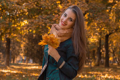 Cheerful young girl in the Park keeps the leaves in his hand looks straight and smiling Royalty Free Stock Photography