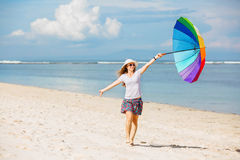 Cheerful young girl with rainbow umbrella having Stock Images
