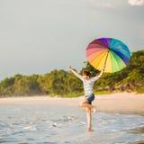 Cheerful young girl with rainbow umbrella having Stock Photo