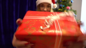 Cheerful young girl in santa hat dancing and smiling with christmas gift in hands stock video footage