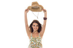 Cheerful young girl in sarafan with floral patter and straw hat with wide brim smiling and looking at the camera Stock Photos