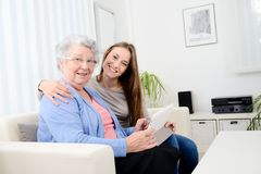 Cheerful young girl sharing time with an old senior woman and teaching internet with a computer tablet Stock Photo