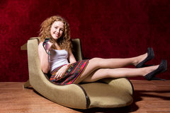 Cheerful young girl sitting on a chair fashion on a red backgrou Stock Photography