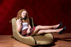 Cheerful young girl sitting on a chair fashion on a red backgrou Stock Photo