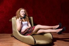 Cheerful young girl sitting on a chair fashion on a red backgrou Royalty Free Stock Photo