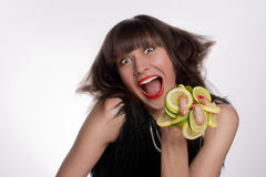 Cheerful young girl smiles and squeezes fresh lemons and limes. Fresh juice from lemons and limes squeezed by a young laughing girl with a funny haircut. Ideal Royalty Free Stock Photography