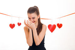 A cheerful young girl stands near Red Ribbon with hearts hanging its head down and keeps hands near individuals. Is isolated on a white background Stock Photos