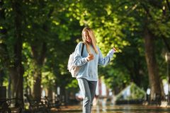Cheerful young girl student with backpack. Holding mobile phone, walking at the park Stock Image