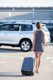 Cheerful young girl with suitcase is ready for. Cute fit woman is standing near her car at the airport. She is moving with her luggage confidently. Focus on her Royalty Free Stock Photography